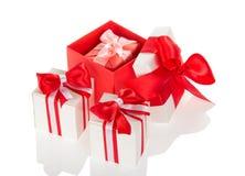 Яркие праздничные коробки для подарков, украшенные при ленты и смычок изолированные на белизне Стоковое Фото