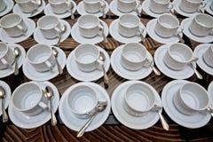 Яркие пустые чашка и поддонник на таблице Стоковые Изображения