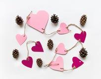 Яркие розовые бумажные сердца соединились с веревочкой на день ` s валентинки Плоское положение на белой предпосылке Стоковое фото RF