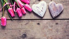 Яркие розовые тюльпаны весны и 2 декоративных сердца Стоковое Фото