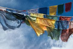 Яркие тибетские флаги молитве с изображениями лотоса и текстами мантры, ветром дуют и ткань порхает, голубое небо с облаками, буд Стоковые Изображения RF