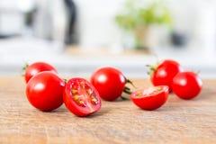 Яркие томаты вишни на деревянной доске и белизне запачкали современную кухню на предпосылке Стоковые Фотографии RF