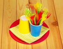 Яркие устранимые бумажные стаканчики, пластичные вилки, плита на освещенной древесине Стоковые Изображения