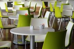 Яркие ые-зелен стулья вокруг таблиц в обедать ресторан Стоковое фото RF