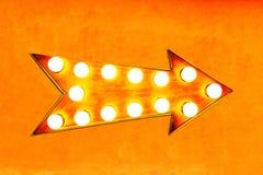 Яркий апельсина, желтых и рыжеватых цвета винтажный и красочный загоренный металлический знак стрелки дисплея на оранжевой стене Стоковые Изображения