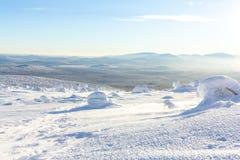Яркий белый снег на горных склонах с горами на горизонте в зиме Стоковые Изображения RF