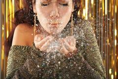 Яркий блеск красивой женщины дуя от рук стоковое фото