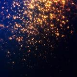 Яркий блеск освещает абстрактную предпосылку Золотое stardust искры на b стоковая фотография