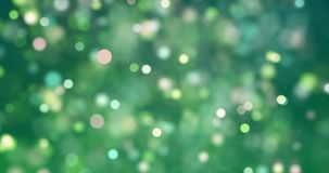 Яркий блеск рождества цифровой искрится зеленое желтое bokeh частиц цвета пропуская на зеленой предпосылке, новой xmas праздника  сток-видео