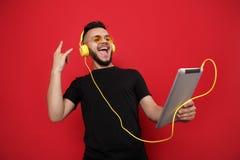 Яркий бородатый человек в желтых солнечных очках и музыка черной футболки слушая на таблетке с счастливой стороной на красном цве стоковая фотография