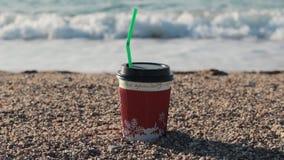 Яркий бумажный стаканчик кофе на песчаном пляже seashore сток-видео