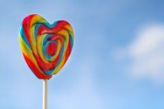 Яркий леденец на палочке радуги на ручке и голубом небе Стоковые Изображения RF