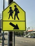 Яркий желтый пешеходный знак Crosswalk рядом с главной дорогой Стоковые Фото