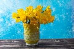 Яркий желтый Narcissus цветет букет в желтой стеклянной вазе, Стоковое Изображение