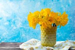 Яркий желтый Narcissus цветет букет в желтой стеклянной вазе, Стоковая Фотография