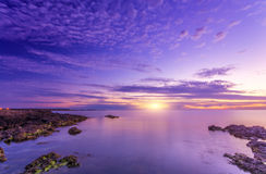 Яркий дивный яркий заход солнца и скалистое seacost Стоковая Фотография