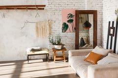 Яркий интерьер с белыми кирпичными стенами, зеркало просторной квартиры, современный свет, софа, оформление Стоковое фото RF