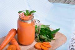 Яркий коктеиль smoothie на голубой предпосылке ткани Здоровый напиток вытрезвителя в опарнике каменщика рядом с морковью и базили Стоковые Изображения RF