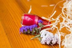 Яркий косметический опарник и высушенные цветки на деревянном столе Стоковые Изображения RF
