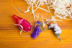 Яркий косметический опарник и высушенные цветки на деревянном столе Стоковые Фотографии RF