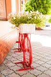 Яркий красный декоративный велосипед стоит на улице с цветками стоковое фото rf