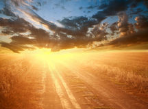 Яркий красочный заход солнца над проселочной дорогой на драматическом небе стоковые фото