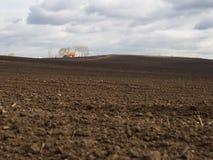 Яркий дом за пахотноспособным полем на гадком дне Стоковая Фотография