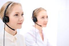 Яркий офис центра телефонного обслуживания 2 белокурых женщины в шлемофоне Стоковое фото RF