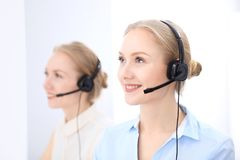 Яркий офис центра телефонного обслуживания 2 белокурых женщины в шлемофоне Стоковое Фото