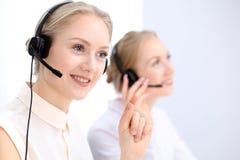Яркий офис центра телефонного обслуживания 2 белокурых женщины в шлемофоне Стоковые Изображения