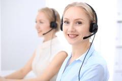 Яркий офис центра телефонного обслуживания 2 белокурых женщины в шлемофоне Стоковые Изображения RF