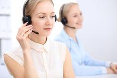 Яркий офис центра телефонного обслуживания 2 белокурых женщины в шлемофоне Стоковое Изображение