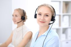 Яркий офис центра телефонного обслуживания 2 белокурых женщины в шлемофоне Стоковая Фотография RF