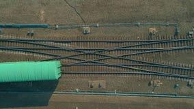 Яркий поезд цвета двигая дальше рельсы, взгляд сверху Летание над железнодорожными путями