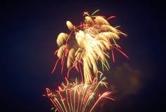 Яркий салют против ночного неба, немножко дунутого прочь ветром, красно-желтым, с зеленой инфлекцией, цвет стоковые фото