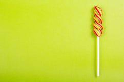 Яркий сочный покрашенный леденец на палочке на зеленой предпосылке Леденец на палочке в форме спирали цвета стоковое фото rf