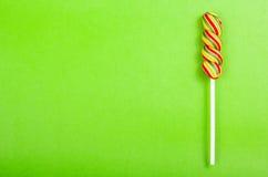 Яркий сочный покрашенный леденец на палочке на предпосылке зеленой книги Леденец на палочке в форме спирали цвета Конфета плодоов Стоковое Фото