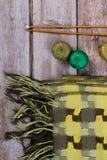 Яркий ый-зелен checkered шарф с пряжей и деревянными спицами Стоковые Изображения