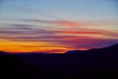 Яркий эффектный заход солнца в горах Стоковые Фото