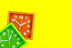 2 ярких будильника на желтой предпосылке Зеленый цвет и апельсин часов таблицы стоковое фото rf