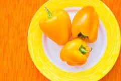 3 ярких желтых перца на конце плиты вверх Стоковые Изображения