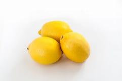 3 ярких желтых лимона на белой поверхности предпосылки Стоковая Фотография