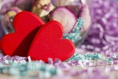 2 ярких красных сердца на предпосылке высушенных роз и бумажной сусали Стоковые Изображения