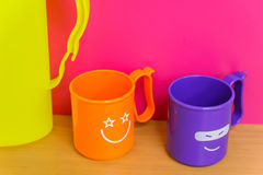 2 ярких пластичных чашки с смешными сторонами на их Стоковое Изображение