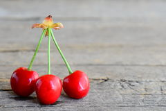 3 ярких сладостных вишни изолированной на винтажной деревянной предпосылке с пустым пространством для текста Стоковая Фотография