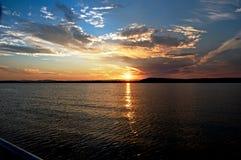 Яркое золото и голубой seascape захода солнца с отражениями воды Стоковая Фотография