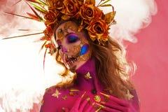 Яркое изображение хеллоуина, мексиканский стиль с черепами сахара на стороне Кожа молодой красивой женщины яркая розовая стоковое фото rf
