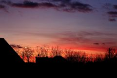 Яркое красное и оранжевое и голубое небо захода солнца против домов и чуть-чуть силуэтов деревьев зима захода солнца гор s вечера Стоковое Изображение RF