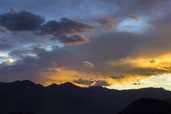 Яркое красочное небо захода солнца над силуэтами горы стоковые фото