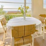 Яркое окно с цветками и плетеными стульями стоковые изображения
